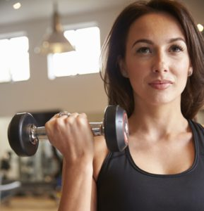 Woman doing bicep curls with dumbbells at a gym, vertical